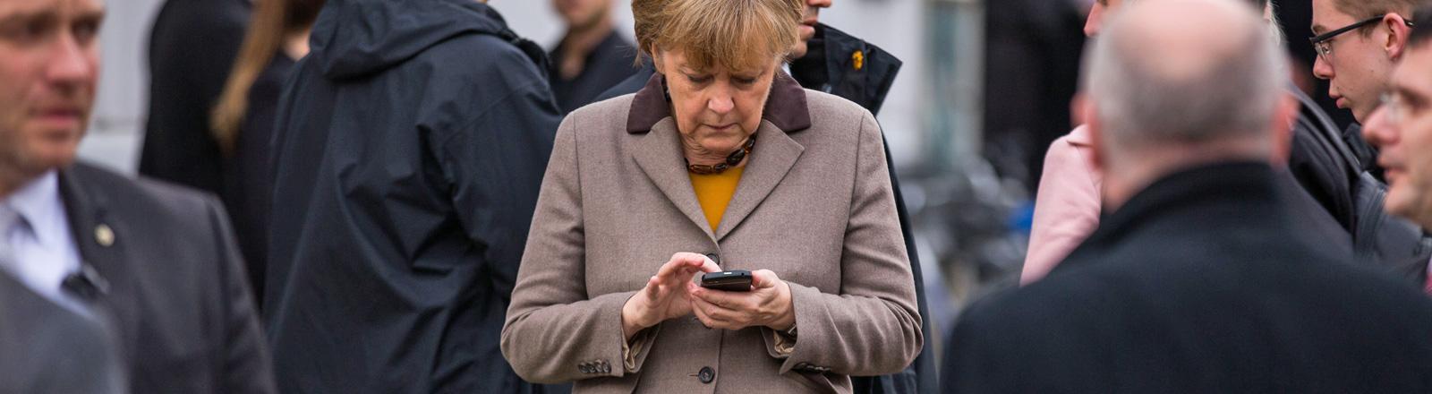 Kanzlerin Angela Merkel tippt eine SMS auf ihrem Mobiltelefon, drumherum stehen Leute (03.11.2014); Bild: dpa