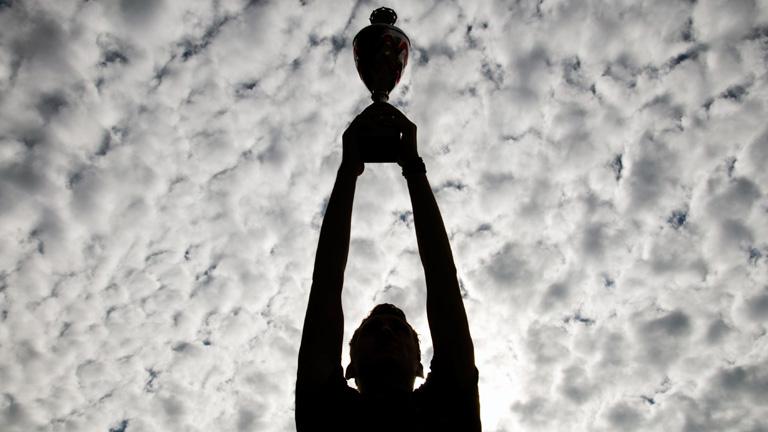 Ein Mann hält einen Pokal in den Himmel mit vielen Schäfchenwolken.