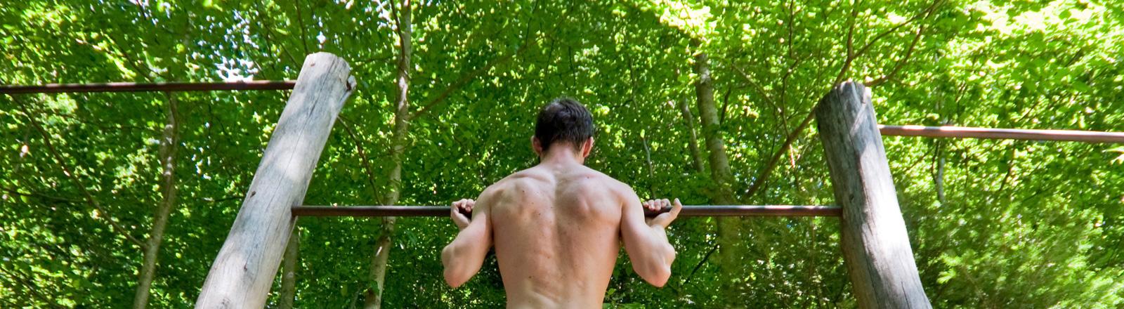 Ein Mann mit nacktem Oberkörper macht an einem Sportgerät im Wald Klimmzüge.