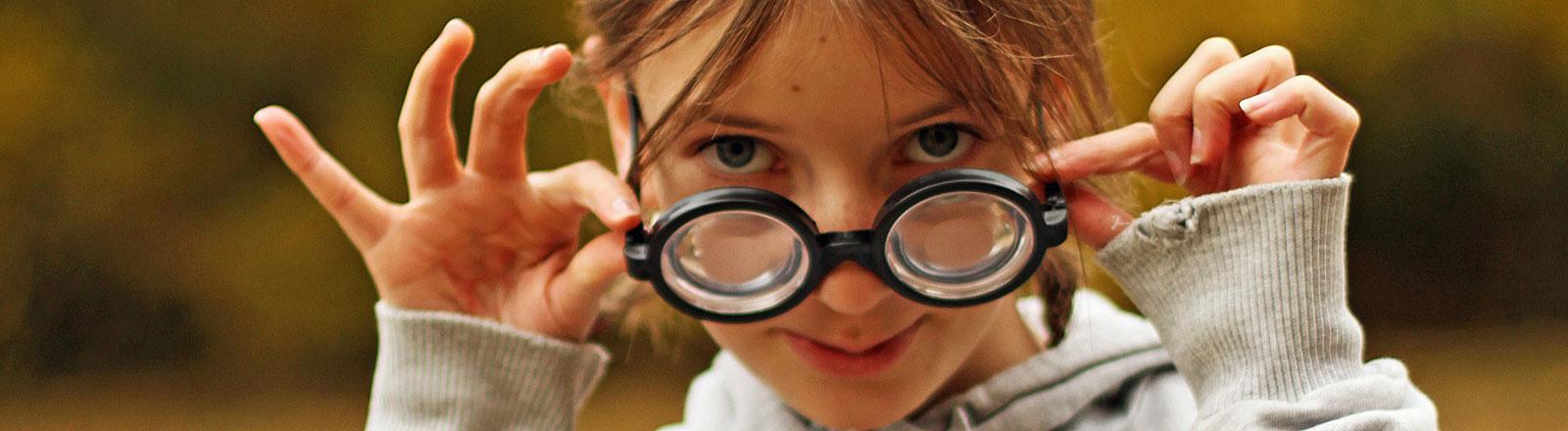 Mädchen greift sich an die Hornbrille