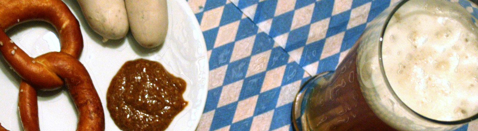 Eine bayrische Mahlzeit mit Brezel, Weißbier und Weißwürsten.