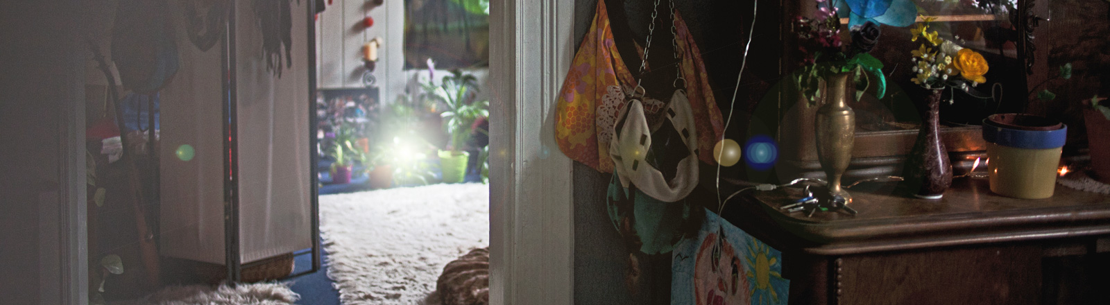 In einer Wohnung steht rechts ein Schrank mit Vasen darauf. Links ist eine Tür geöffnet. Der Blick fällt in einen hell erleuchteten Raum.