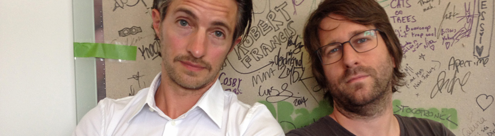 Gregor Iwanoff steht vor der Unterschriftenwand von DRadio Wissen im weißen Hemd.