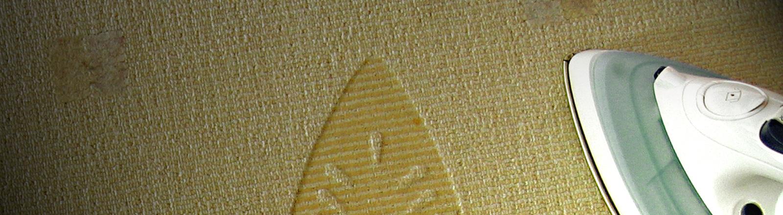 Ein Bügeleisen steht auf einem Teppich. Daneben ist der Abdruck des Bügeleisens im Teppich erkennbar.