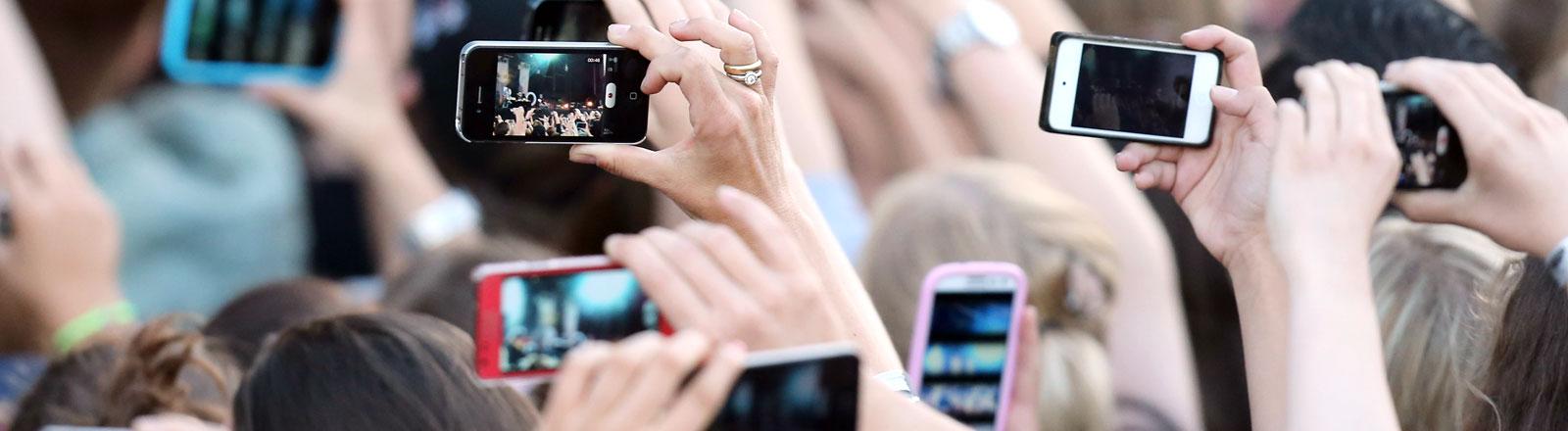 Menschen halten bei einem Konzert Mobiltelefone in die Luft.