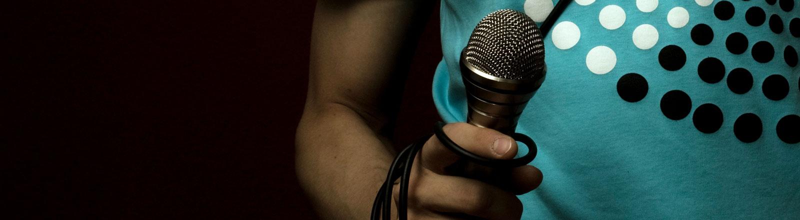 Ein Musiker mit Mikrofon in der Hand.