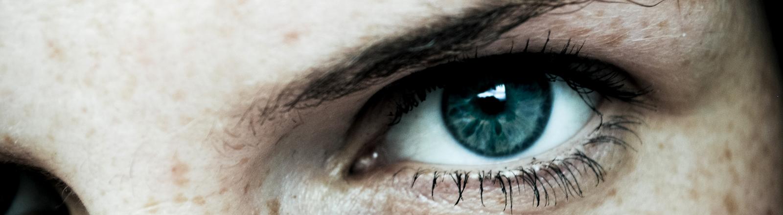 Ein Auge mit hochgezogener Augenbraue