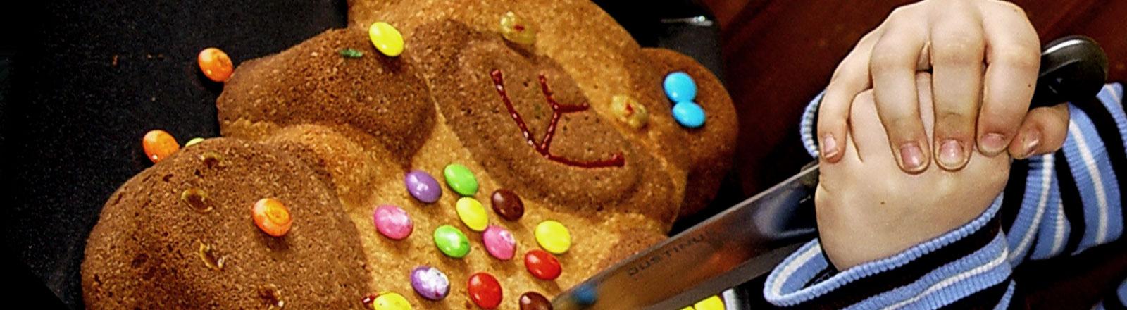 """Ein Geburtstagskuchen in der Form eines Teddybären wird von einem Messer """"erstochen""""."""