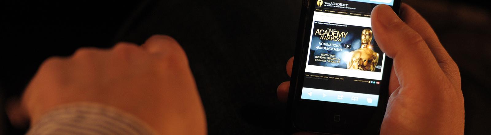 Mann hält ein Smartphone und ruft die Seite der Oscar-Nominierungen auf.