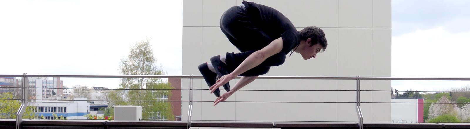 Jessaja Latala von Zero Gravity fliegt auf der DRadio-Wissen-Terrasse über einen Gartentisch.
