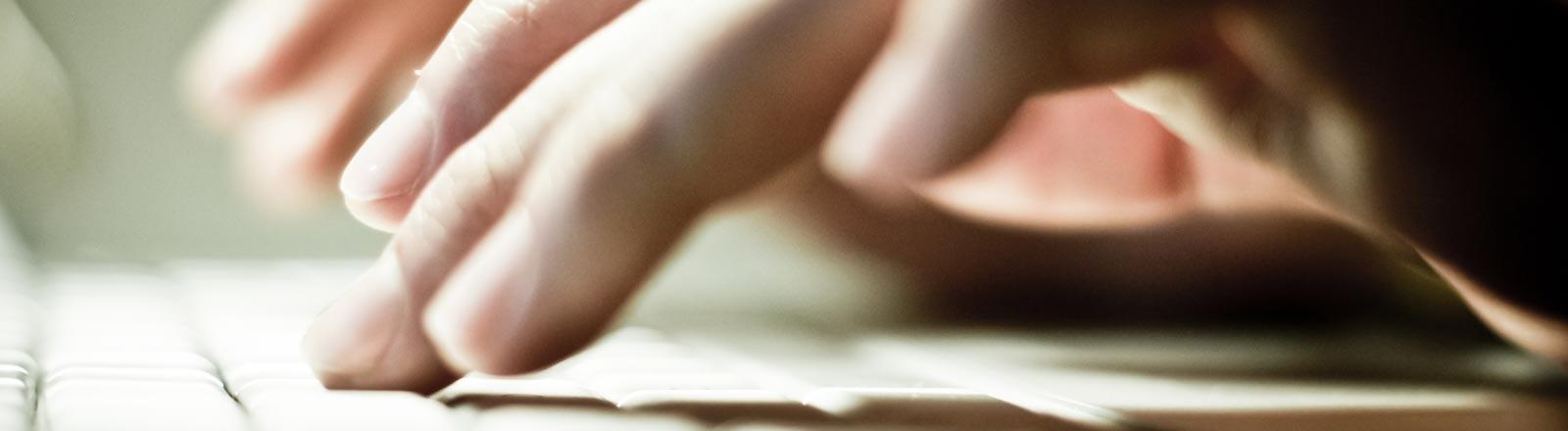 Eine Person schreibt auf einer Computertastatur.