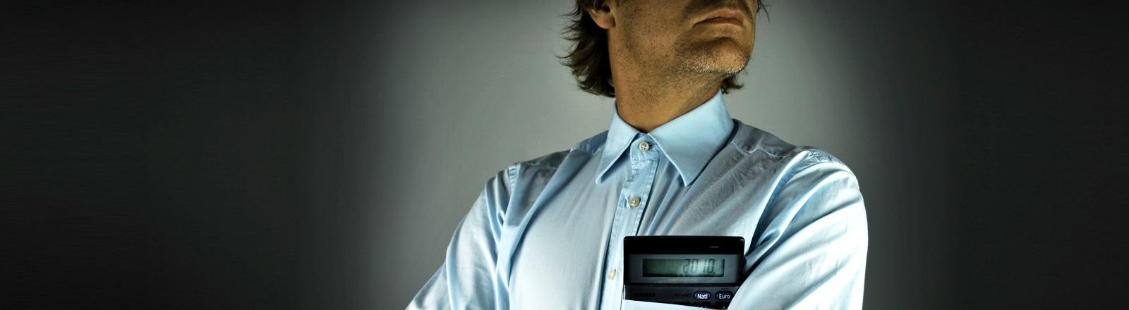 Ein Mann mit Hemd und Taschenrechner in der Brusttasche.