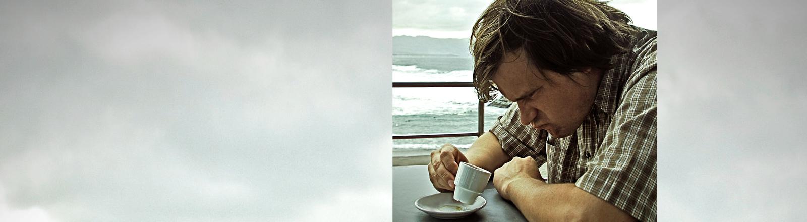 Mann blickt frustriert in Kaffeetasse.