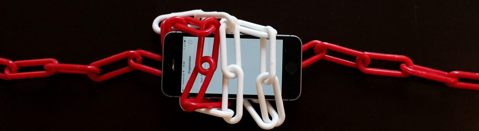 Ein Smartphone mit einer Kette umwickelt.