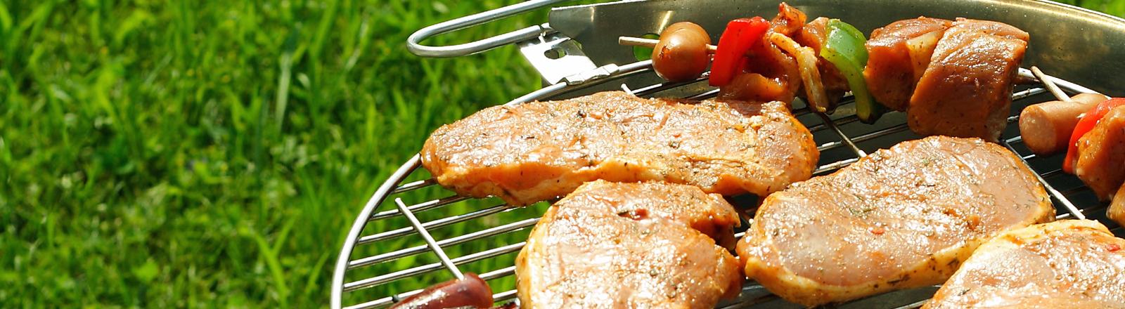 Ein Grill mit Fleisch beladen.