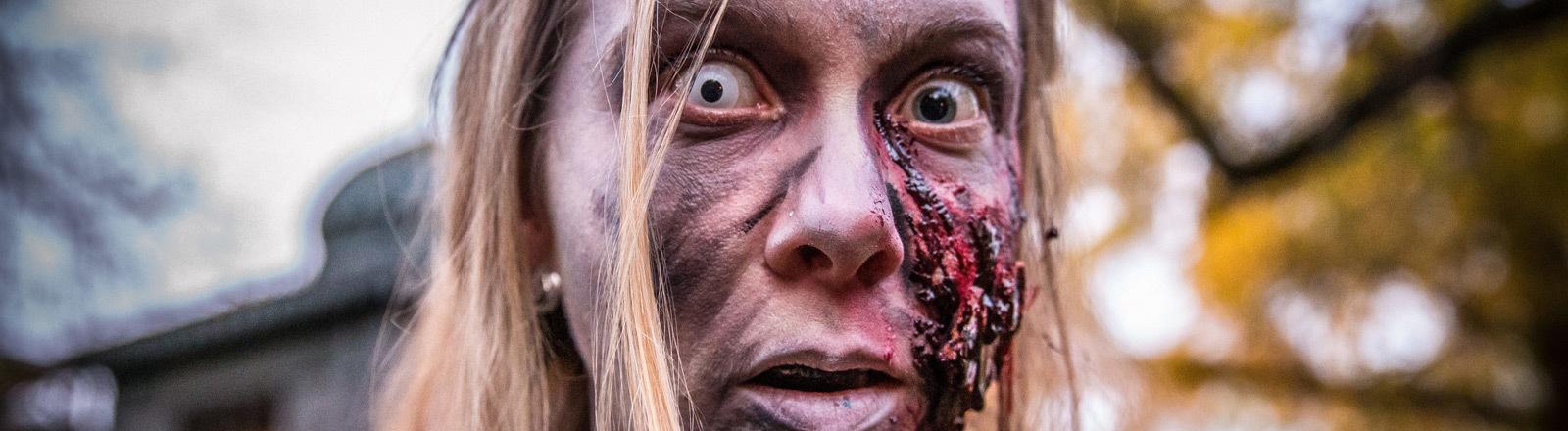 Eine Frau, die sich als Zombie geschminkt hat.