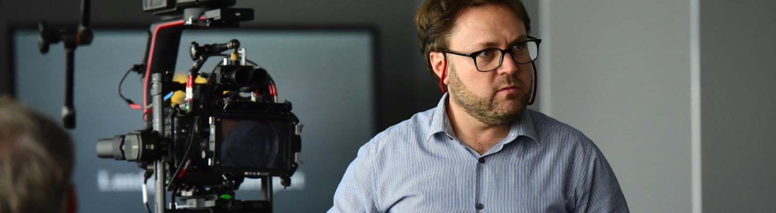 Filmemacher Daniel Harrich steht neben einer Kamera