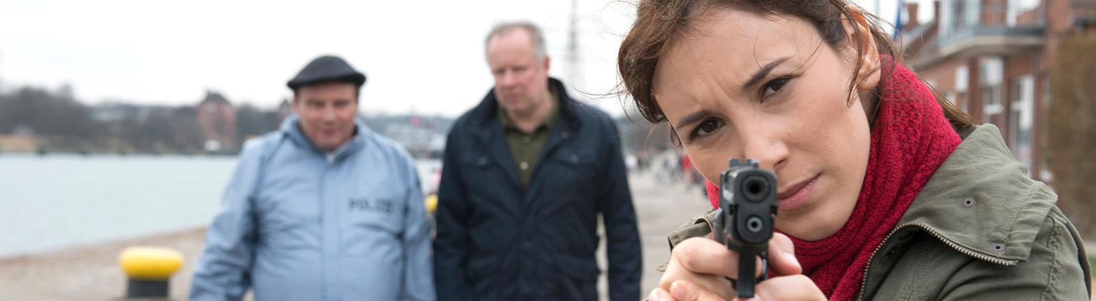 Tatort: Borowoski und das  Meer. Sarah Brandt (Sebil Kekilli) hält eine Waffe in der Hand. Borowski (Axel Milberg) und Klee (Jan Peter Heyne) schauen zu.