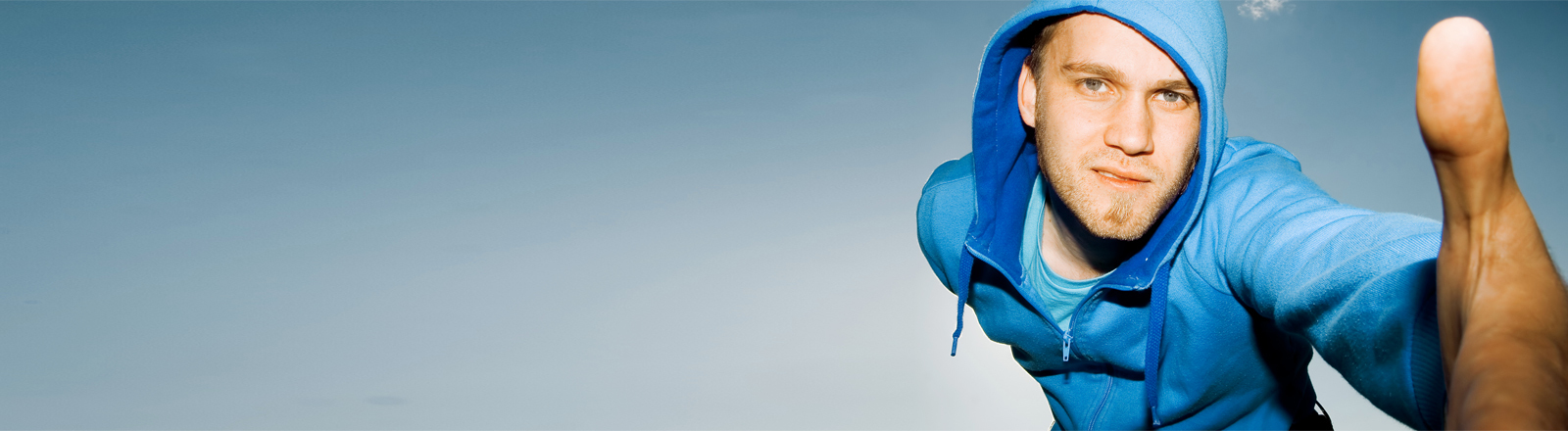 Ein junger Mann in blauem Kaputzenpulli streckt die Hand Richtung Kamera.