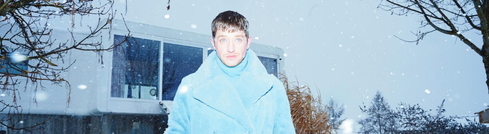 Im Schnee und zwischen Bäumen: der Rapper und Musikproduzent Maeckes, geblitzt im Garten