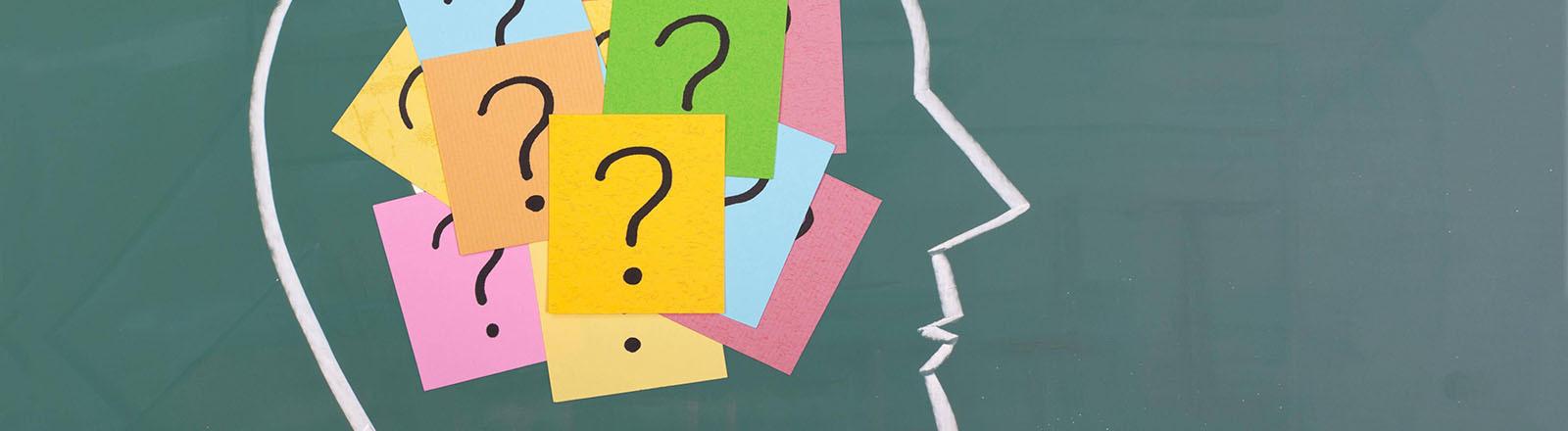 Ein mit Kreide auf eine Tafel gezeichneter Kopf, darin befinden sich Post-its, auf die ein Fragezeichen gezeichnet ist.