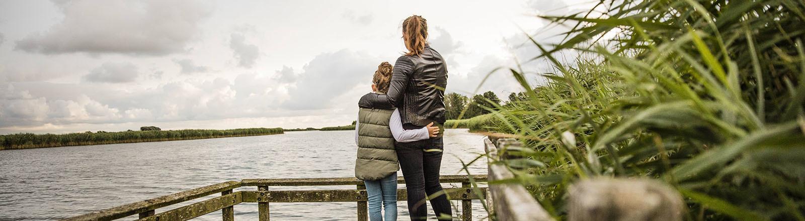 Mutter und Tochter Arm in Arm.