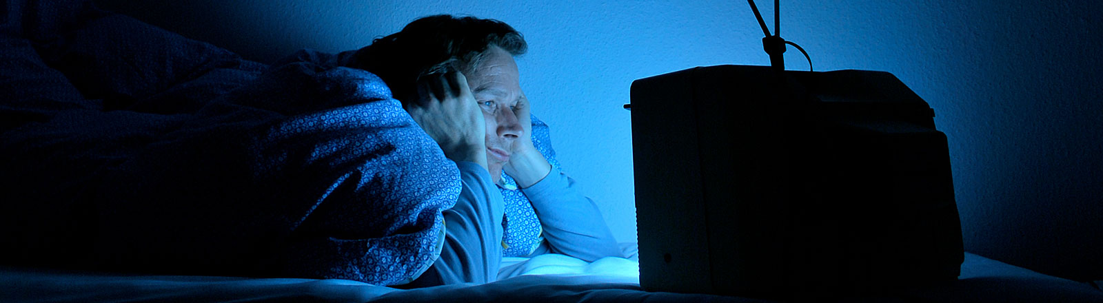 Mann schaut genervt Fernsehen