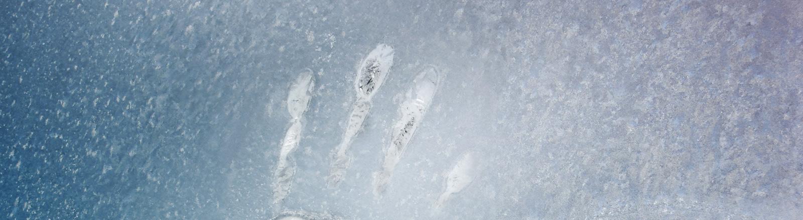Handabdruck an einer frostigen Scheibe.