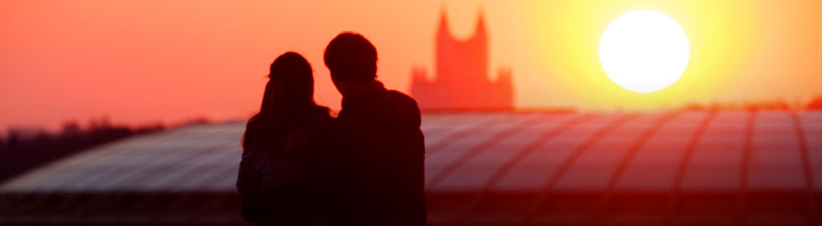 Ein Mann und eine Frau betrachten eine Stadt beim Sonnenuntergang
