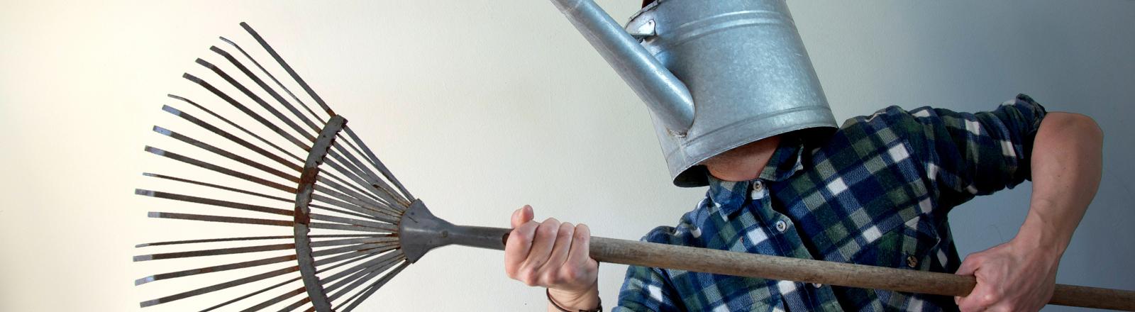 Ein Mann, bewaffnet mit einer Harke und einer Gießkanne auf dem Kopf.