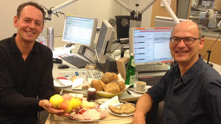 Moderator Manuel Unger und Gast Valentin Thurn sitzen im Studio, zwischen ihnen liegen auf dem Tisch Brötchen, Käse, Äpfel.