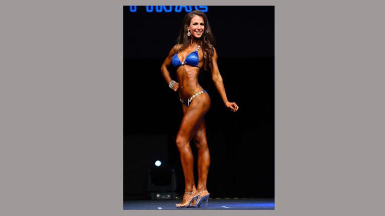 Kathrin Weishaupt bei einem Wettbewerb. Sie trägt einen blauen Bikini und silberne High Heels.