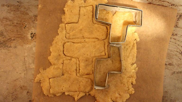 Die Plätchenformen arbeiten sich fast wie Rasierklingen durch den ausgerollten Teig. Ab in den Ofen!