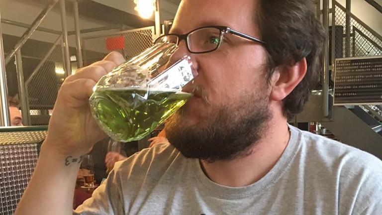 Reinhard Remfort mit Brille und Bart. Er trinkt aus einem großen Bierglas eine grüne Flüssigkeit.