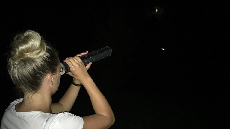 Rahel Klein schaut durch ein selbst gebasteltes Fernrohr.