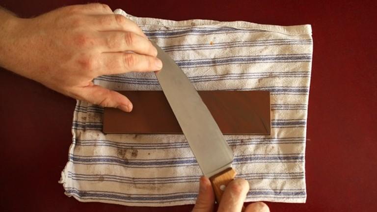Ein Messer wird mit einem japanischen Wasserschleifstein geschliffen.