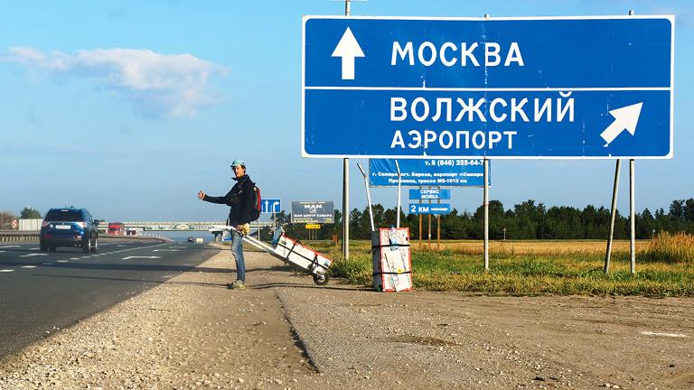 """Ein junger Mann trampt an einer Autobahn neben einem Schild """"Moskau""""."""