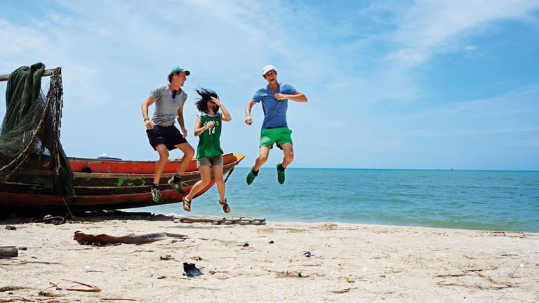 Drei junge Leute am Strand springen hoch.