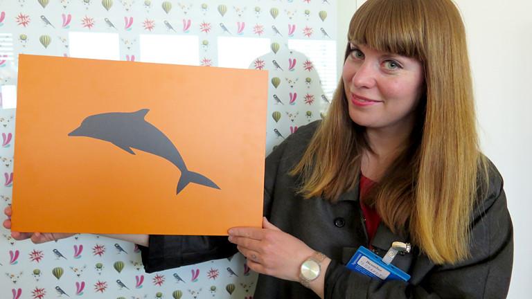 Frau mit einem Delphin-Schild in der Hand.