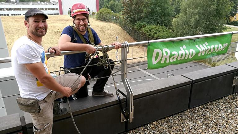 Industriekletterer Johannes Müller (l.) erklärt DRadio-Wissen-Moderator Sebastian Sonntag, was er zu tun hat