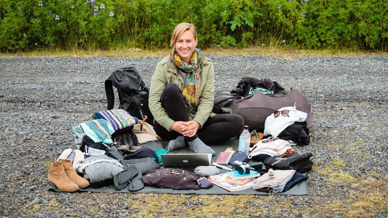 Katharina Finke sitzt zusammen mit ihrem Reisegepäck auf einer Decke