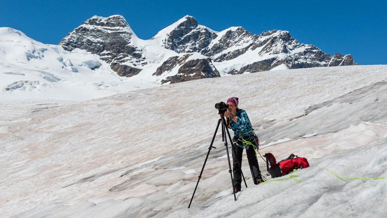 Caroline Fink beim Fotografieren in schneebedeckten Bergen