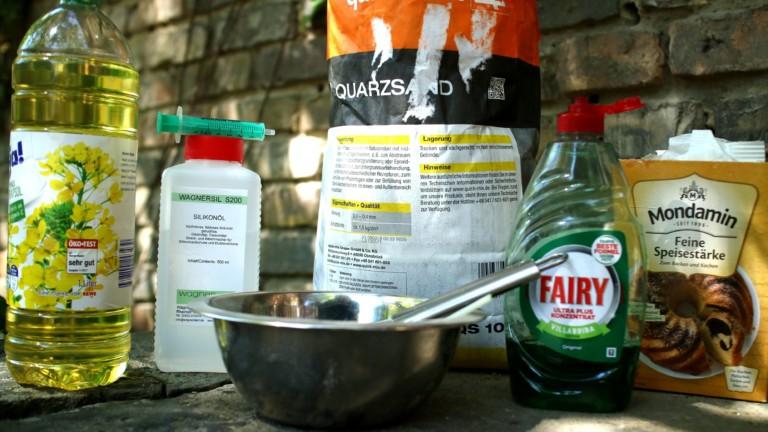 Speiseöl, Quarzsand, Spülmittel, Speisestärke und eine Metallschüssel