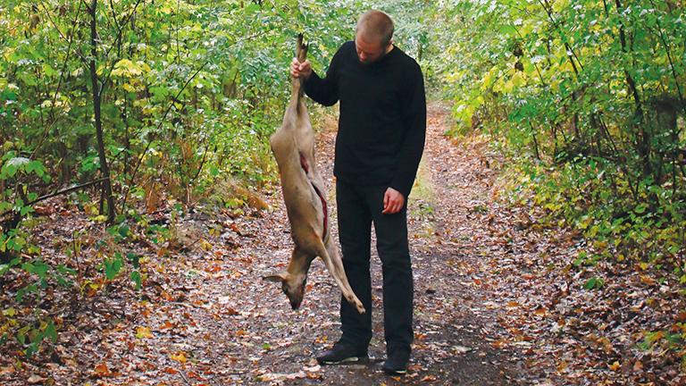 Der Jäger Fabian Grimm mit einem ausgenommenen Rehkitz