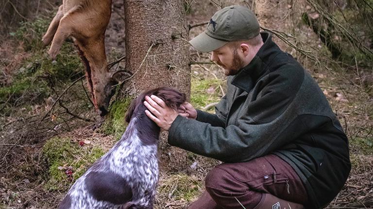 Der Jäger Fabina Grimm mit seinem Jagdhund Kira und einem erlegten Reh.