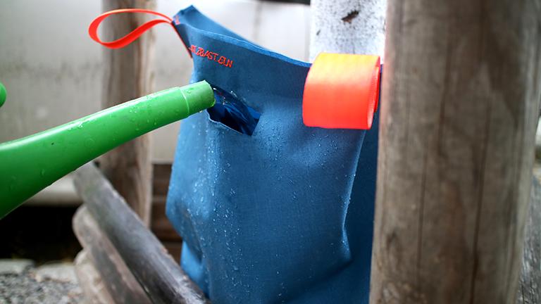 Ein Baumbewässerungssack wird mit einer Gießkanne aufgefüllt.