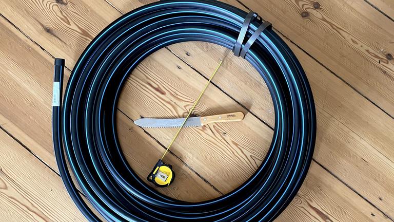 Von einer einer 25mm-Polyethylen-Kaltwasserleitung aus dem Baumarkt schneidet Moritz ungefähr 3,14m ab, das entspricht einem Reifen-Durchmesser von 1 Meter - gerade bei Anfängern sollte der der Ring auf dem Boden stehend mindestens bis zum Bauchnabel reichen.