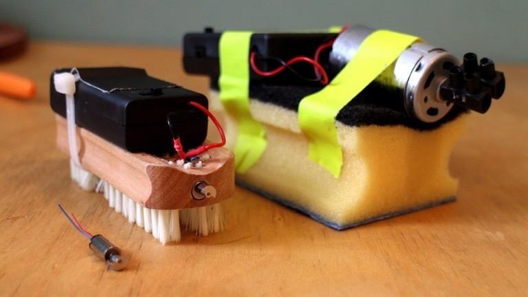 Gestatten, die Roboter-Putzkolonne! Broomba nutzt einen Handy-Vibrationsmotor, Spoonba den Antrieb eines Modellbauflugzugs.