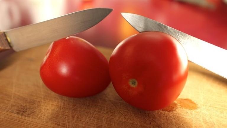 Zwei Messer schneiden zwei Tomaten.