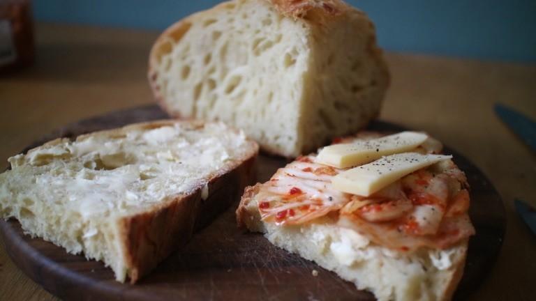Scheiben selbstgebackenen Sauerteigbrotes bestrichen mit Mutter und belegt mit Kimchi und Käse.